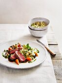 Poached saddle of lamb with mint couscous and spring vegetables