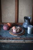 A rustic arrangement with a pewter jug, a salt shaker and beetroots on pewter plate