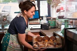 A woman in a bakery with a tray of doughnuts