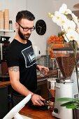 Junger Mann bei der Kaffeezubereitung im Cafe
