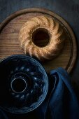 A Bundt cake and an empty baking tin on a wooden board on a dark wooden surface with a grey cloth