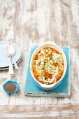 Gratinated spinach-filled pasta parcels with tomato sauce and feta cheese