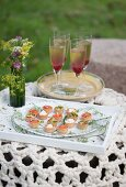 Dish of various canapés and Champagne cocktails in stemmed glasses on garden table