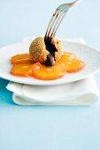 Schokoknödel (angeschnitten) auf kandierten Mandarinen
