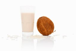 A glass of coconut milk with coconut and grated coconut next to it