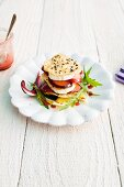 A cheese and plum tower with crispy sesame seed chips