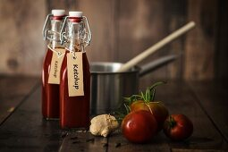 Bottle of homemade ketchup with ingredients and kitchen utensils on a wooden table