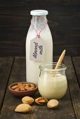 A jar of almond mousse and almond milk in a glass bottle