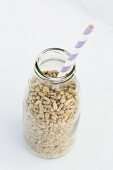 Sunflower seeds in a milk bottle with a straw