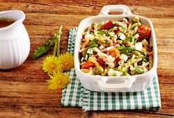 A pasta salad with dandelions, tomatoes and olives