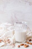 A glass of almond milk, next to whole and ground almonds