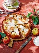 Sunken apple cake with a sour cream glaze, sliced
