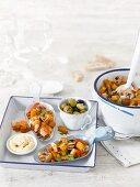 Seafood tapas with crispy potatoes, olives and aioli