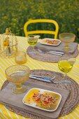 Orangendessert für Zwei auf gelb-weiß gestreifter Tischdecke und rustikalen Tischsets