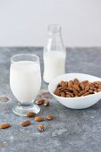 Whole almonds, and almond milk in a glass and in a bottle