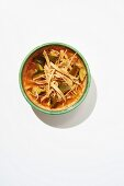 Spicy tortilla soup with chicken stock, tortilla strips, chicken, roasted vegetables and coriander