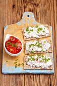 Crisp bread with cottage cheese, radishes and spring onions served with tomato salad