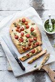 Focaccia mit Tomaten und Pesto, angeschnitten (Draufsicht)
