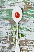 Strawberry jam on a spoon and strawberry flowers on a wooden table