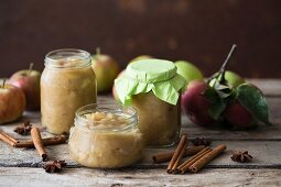 Jars of apple sauces, spices and fresh apples