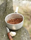 Bolognese sauce, a pocket knife and cheese for camping on a rocky ledge