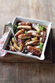 Sausages baked with mustard and pears