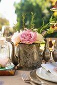 Roses in teapot decorating tea-time buffet