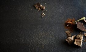 Various types of cooking chocolate and cocoa powder on a grey surface