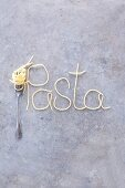 The word 'pasta' written in spaghetti with a fork