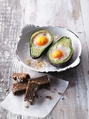 Eggs in an avocado baked in the oven served with wholemeal bread