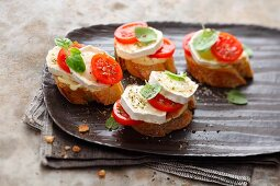 Canapés with goats cheese, cocktail tomatoes and oregano
