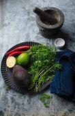 Zutaten für Guacamole auf schwarzem Metallteller