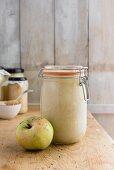A jar of apple sauce and fresh apple