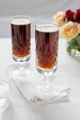Two glasses of dark beer with a bunch of roses in the background