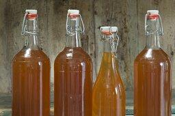 Bottle of apple juice with a flip-top jar on a rustic shelf