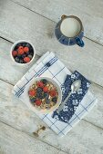 A healthy breakfast: muesli with milk and fresh berries (seen from above)