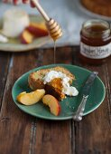 A slice of chiffon cake with olive oil served with cheese, nectarines and honey