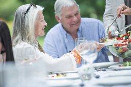 A family garden party: a woman serving an older woman salad