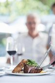 A meat dish and a glass of red wine on a summer table outside with a person in the background