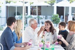 A family celebrating a grandfather's birthday on the terrace of a restaurant