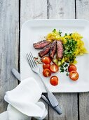 Beef steak with a herb potato salad, gherkins and tomatoes