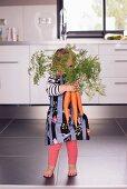 A little girl hiding behind a bunch of carrots
