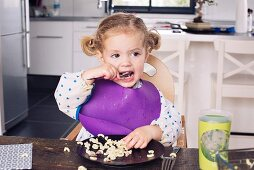A little girl sitting in a high chair eating lunch