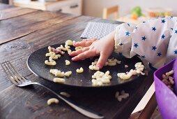A child taking elbow macaroni