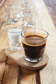 A glass of coffee and a shot glass of milk