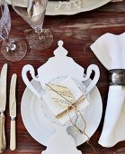 White place setting with vintage-style paper decoration on wooden table