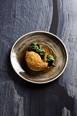 Guinea fowl breast with a peanut and lemon rust and orange spinach (Turkey)