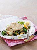 Chicken breast with potatoes, peas and baby corn on parchment paper