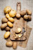 Kartoffeln mit Schneidebrett und Kartoffelschäler