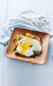 Grilled polenta slices with a fried egg and sage
